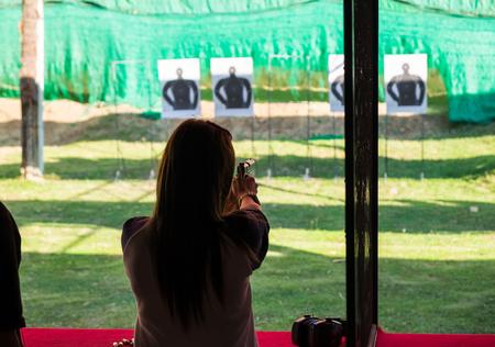 Woman practice shooting pistol in shooting gallery