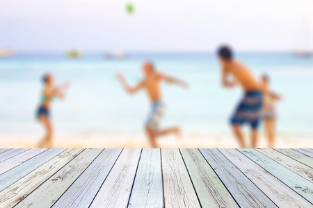 White wood table on blurred young tourists playing ball on beach background Stock Photo