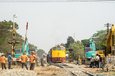 Train and backhoe worker improvement construction of railway