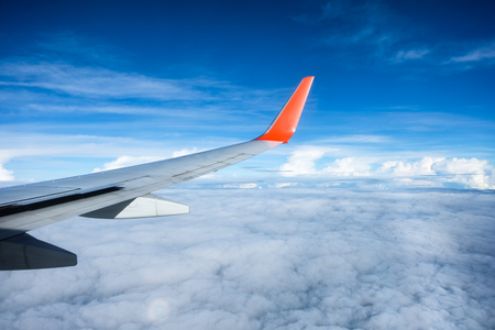 Wing of airplane flying on blue sky
