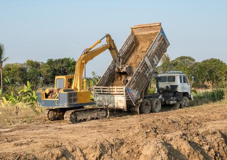 Yellow backhoe digging soil fill on rear truck