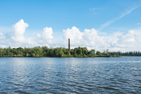 Blue water and tropical mangrove with brick tower in reservoir Stock Photo