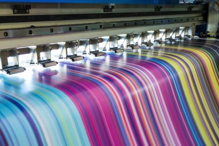 Impresora de inyección de tinta grande que trabaja cmyk multicolor en banner de vinilo Foto de archivo
