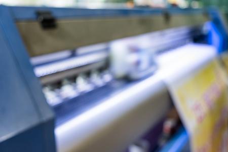 El color del cabezal de impresión de inyección de tinta de escena borrosa trabaja en un banner de vinilo amarillo Foto de archivo