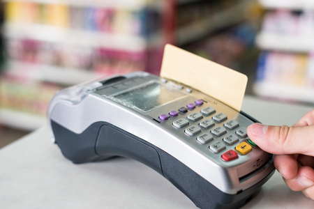 Hand press with swiping credit card on payment terminal in supermarket