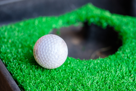 Golf ball edge hole cup on green lawn Stock Photo