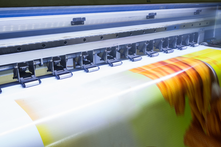Format large inkjet printer working on yellow vinyl banner 免版税图像