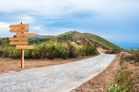 Mountain hill rural roadway with wooden signboard Stok Fotoğraf