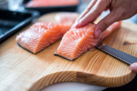 Hand chef using knife slice raw salmon on chopping block