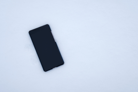 Turn off blank display smartphone falling on snow background