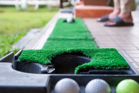 Golfer preparing on training putt with golf ball on mini golf