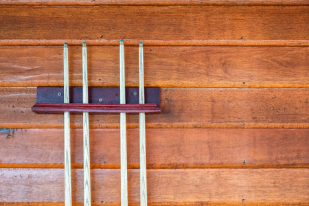 Collection of wooden cue or sticks on wood wall for snooker and billiards Фото со стока