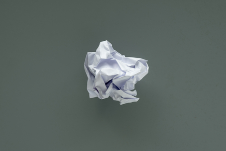 Crumpled paper ball, top view on gray background