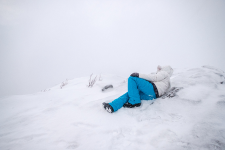 Man mountaineer wearing snow coat with relaxing on snowy peak