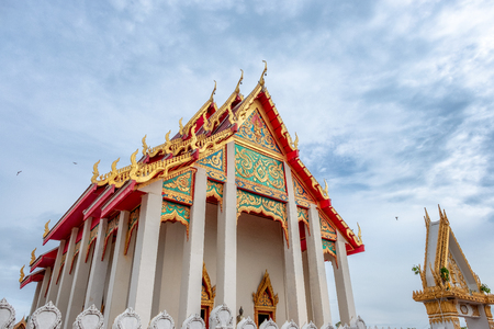 Ancient buddhist chapel with Thai motifs decorated with blue sky in Thailand
