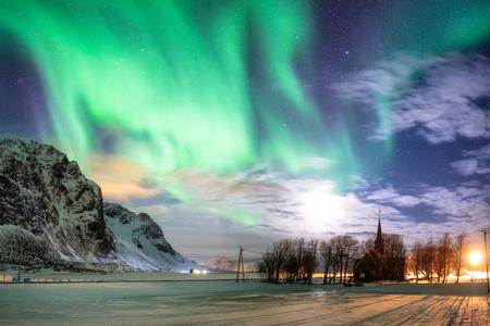Aurora borealis (Northern lights) with stars over Christian church at Skagsanden beach, Lofoten islands, Norway