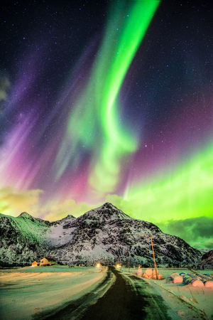 Aurora Borealis (Northern lights) explosion over mountains and rural road at Skagsanden beach, Lofoten island, Norway