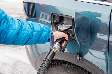Hand hold refueling nozzle self-service in fuel tank at fuel station in winter
