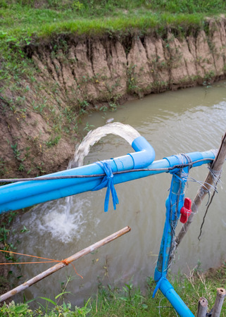 Blue pump pipe water flow down canal