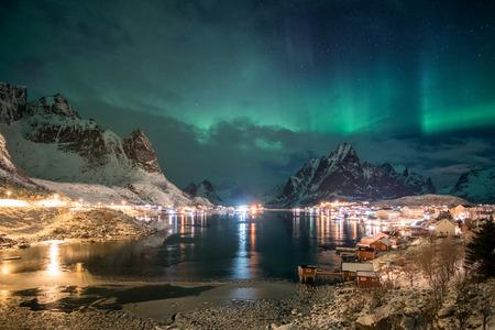 Aurora borealis over scandinavian village light shining in winter at night
