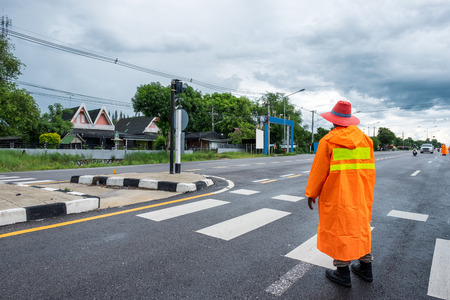 Traffic officer wearing orange raincost with control and directing traffic on crosswalk