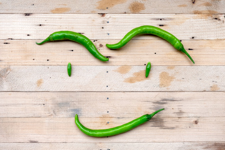 Green chili thai pepper arranged in a manner smiling face on wooden table