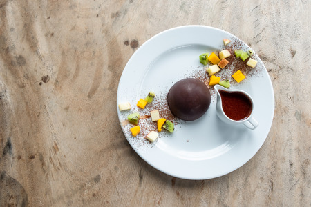 Chocolate cocoa dome dessert with slices fruits on wooden table
