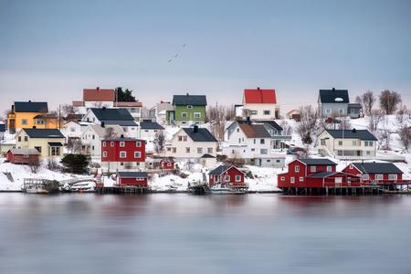 Colorful scandinavian wooden house on snowy at coastline. Lofoten Islands, Norway Stock Photo