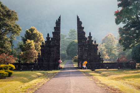 Ancient bali gate with shining pathway in garden