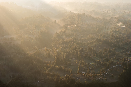 Above of Sunlight on tropical forest with fog on village at morning