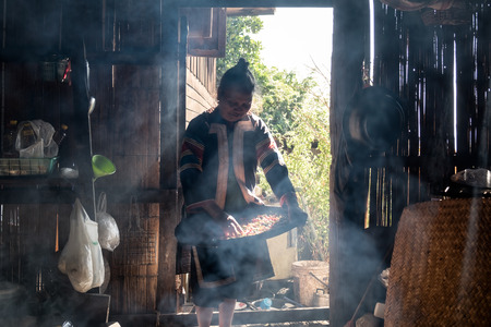 Mae Hong Son,Thailand - Dec 25 2016 : Grandmother lahu muser tribe hold chili wooden tray in traditional kitchen filled with smoke sunlight shining Banque d'images - 115361051