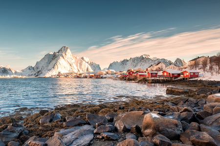 Scandinavisch vissersdorp met besneeuwde berg aan de kust. Reine, Lofoten eilanden, Noorwegen Stockfoto