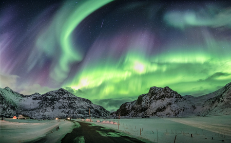 Aurora borealis, Northern lights over snow mountain range at Flakstad, Lofoten islands, Norway