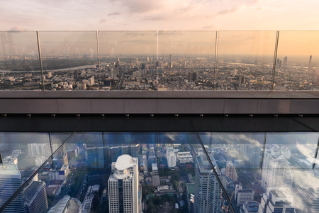 Glass terrace with bangkok city on rooftop at evening