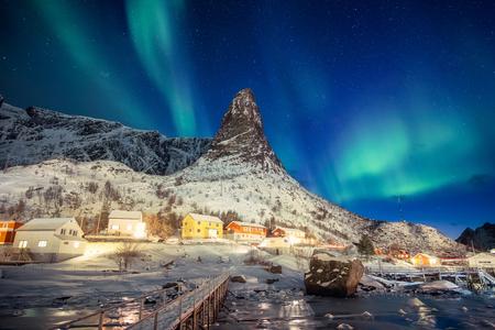 Colorful scandinavian village with northern lights over peak mountain at Lofoten islands