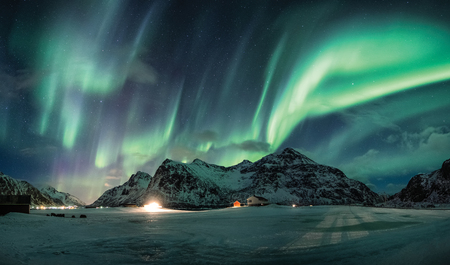 Aurora borealis or Northern lights over snow mountain on coastline in Flakstad, Lofoten islands