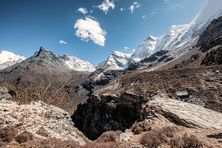 Panorama of snow mountain range in rocky valley at Yading nature reserve