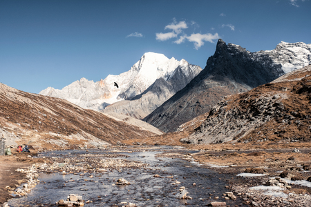 Rock mountain with river flowing and blue sky near Milk lake at Yading nature reserve 写真素材