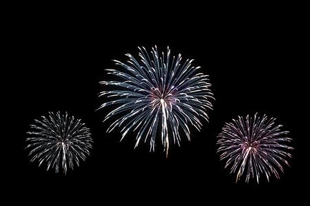 Celebration of colorful fireworks explosion, isolated on black background Imagens