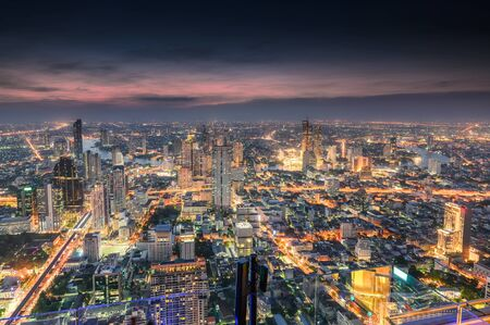 Cityscape of colorful crowded building with light traffic at Bangkok city at dusk