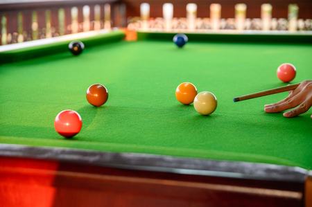 Mans hand playing snooker in bar with color snooker ball