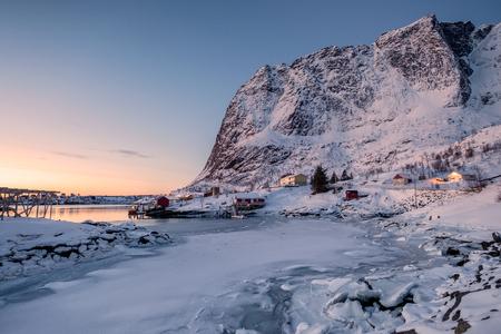 Sunrise on Lofoten archopelago with scandinavian village in valley on winter