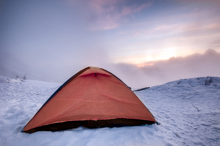 Camping orange tent on snowy hill in sunrise morning