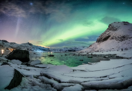 Northern lights explosion on snowy mountain range near coastline at Lofoten islands, Norway Фото со стока
