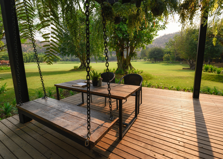 Wooden chair with table and green flora on patio Imagens