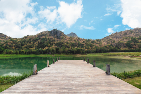 Empty wooden bridge or jetty with mountain and blue sky on lake