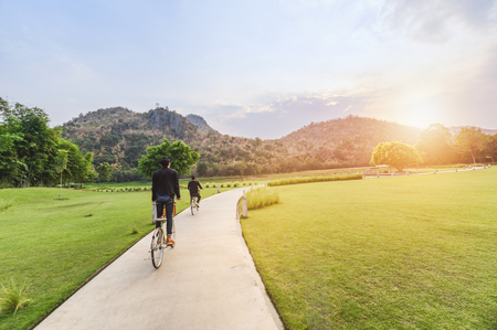 Young man riding retro bicycle in public park with sunlight