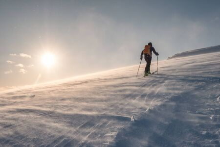 Skier with backpacker hiking on snow hill in blizzard at sunset