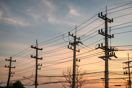 Rural rows of electricity pole with wires network on sunset Imagens