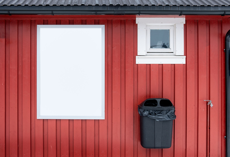 White banner on red wooden wall with trash can at store Imagens